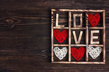 Valentine's day background with love and hearts in the box on wooden table. Copy space for text, top view.