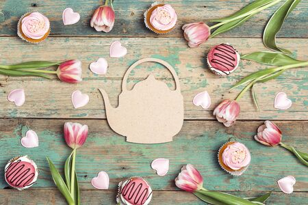 Teapot symbol with cupcakes and tulips on old wooden table. St. Valentine, Mothers, Womens Day concept. Copy space, overhead shot. Festive romantic tea party.