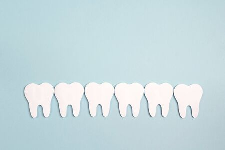 White paper teeth on blue background. Dental health concept. Dentist day concept. Flat lay, top view, copy space for text. Standard-Bild