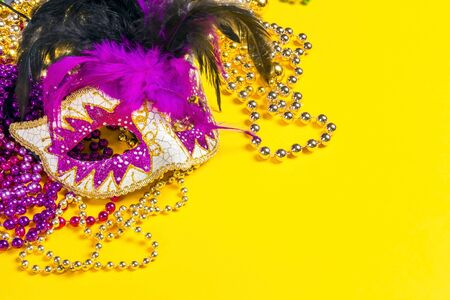 Festive Carnival mask and beads on yellow background with copy space. Stockfoto