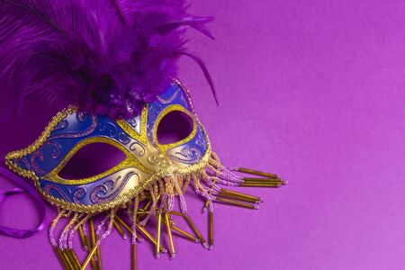 Carnivale mask with purple feathers on a purple background with copy space.