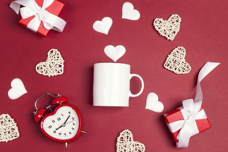 White coffee mug with alarm clock, gifts and decorative hearts on red background. Space for text or design. Valentine's Day Concept. Banco de Imagens