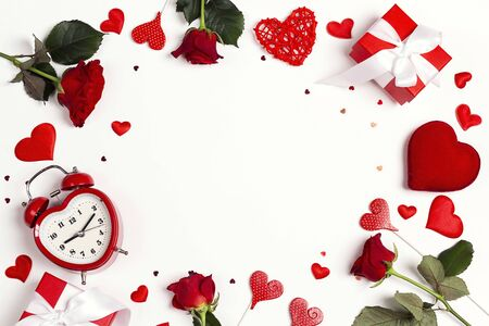 Romantic frame of rose flowers, alarm clock, gifts and decorative hearts on white background. Copy space for text, top down composition. St. Valentines Day concept. Stockfoto