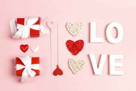 St. Valentines Day composition with word love, gifts and decorative hearts on pink  background. Top down composition,flat lay.