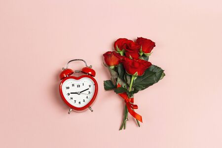 Bouquet of red rose flowers with alarm clock on pink background. Top down composition. St. Valentines Day concept.