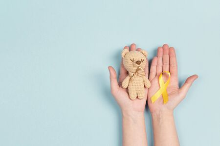Girl hands holding childrens toy with a Childhood Cancer Awareness Yellow Ribbon on blue background. Childhood Cancer Day February, 15. 写真素材