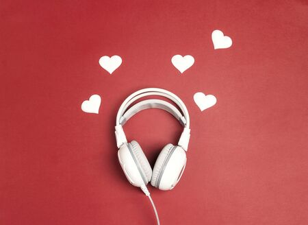 White headphones with heart on red background. Romantic music concept. St. Valentines Day concept. Flat lay, top view.