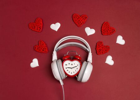 White headphones with  alarm clock and hearts on red background. Romantic music concept. St. Valentines Day concept. Flat lay, top view.