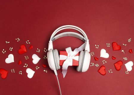White headphones with gift box and decorative hearts on a red background. St. Valentines Day music gift concept. Flat lay, top view.