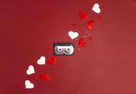 Audio cassette tape with hearts on red  background.  Place for song title. Romantic mood music concept. St. Valentines Day. Flat lay, top view.