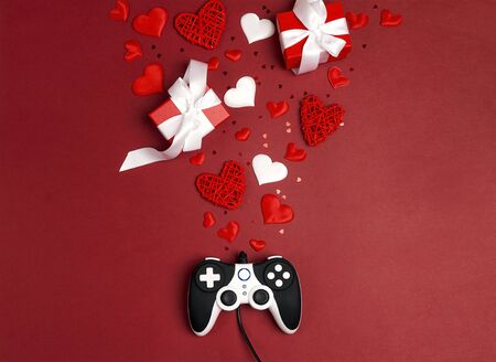 Joystick with romantic decorations on red background. Holidays gaming concept. St. Valentines Day concept. Flat lay, top view.