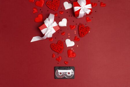Audio cassette tape with gifts and hearts on red background. Romantic mood music concept. St. Valentines Day. Place for song title. Flat lay, top view.