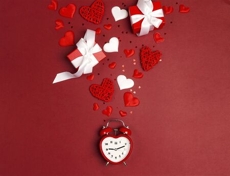 Romantic alarm clock with gifts and hearts on red background. Place for text. Top view, flat lay.