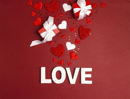 St. Valentines Day background word love, gifts and decorative hearts on red. Top down composition. 写真素材