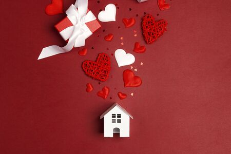 Miniature white toy house with hearts and gifts on red background. St. Valentines Day composition. 写真素材