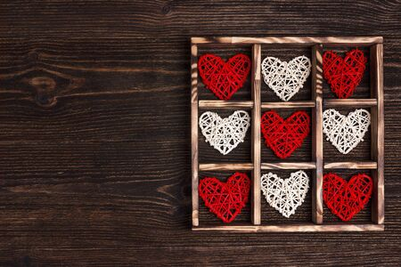 Valentines day background with hearts in the box on wooden table. Copy space for text, top view.