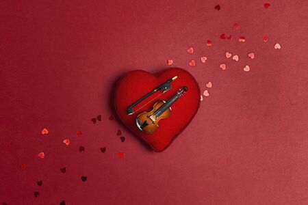 Miniature violin on the heart on the red background. Love for music concept. St. Valentines Day.