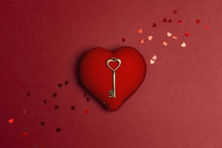 Romantic heart with antique key on red background. The metaphor of the key to heart. St. Valentines Day concept. Flat lay, top view. 写真素材
