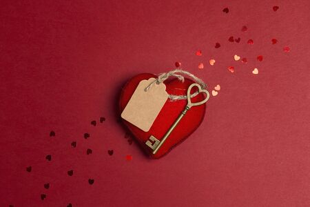 Romantic heart and antique key with blank label on red background. The metaphor of the key to heart. St. Valentines Day concept. Flat lay, top view, copy space.