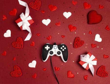 赤い背景にロマンチックな装飾が施されたジョイスティック。休日のゲームの概念。聖バレンタインデーのコンセプト。フラットレイ、トップビュー。 写真素材