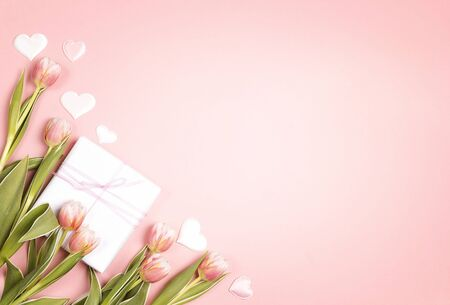 Romantic floral background with tulips flowers, gift and hearts on pink pastel background. Copy space, flat lay, top view.  写真素材