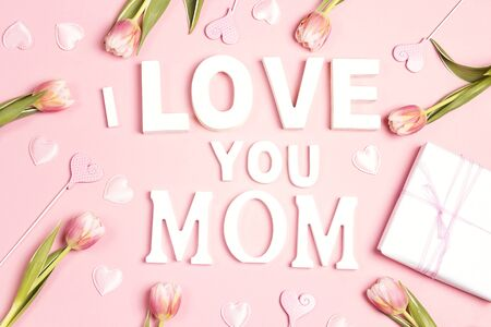 Mothers day message with tulips and hearts on pink background. Flat lay, top view. Mothers day concept.