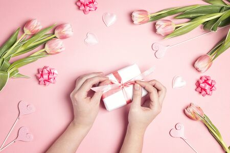 Womens hands decorate gift box surrounded tulip flowers and hearts on pink pastel background. Top-down holiday spring composition. 写真素材