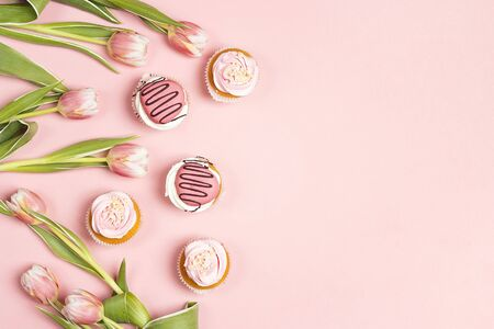 Tasty cupcakes with tulips on pink pastel background. St. Valentine, Mothers, Womens Day concept. Copy space, overhead shot.