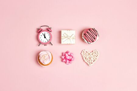 Set of tasty cupcakes, alarm clock, gift and heart on pink pastel background. Romantic love background. St. Valentine, Mothers, Womens Day concept. Copy space, overhead shot.
