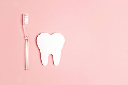White paper tooth with toothbrush on pink background. Dental health concept. Dentist day concept. Flat lay, top view, copy space.