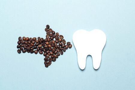 Tooth and coffee bean arrow on a blue background. Coffee spoils teeth and makes them yellow. Oral hygiene, dental care concept. Flat lay.