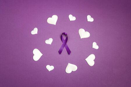 Purple epilepsy awareness ribbon wit white heats on a purple background. World epilepsy day. Purple Day.