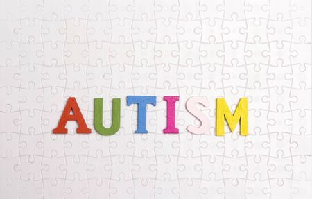 Word Autism on the background of the white puzzle. Autism Awareness Day. Autism Spectrum Disorder (ASD) concept.