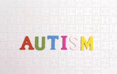 Wort-Autismus auf dem Hintergrund des weißen Puzzles. Autismus-Bewusstseinstag. Konzept der Autismus-Spektrum-Störung (ASS).