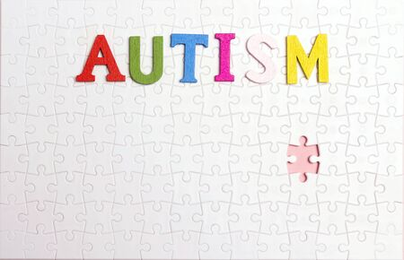 Word Autism on the background of the white puzzle. Autism Awareness Day. Autism Spectrum Disorder (ASD) concept. 写真素材