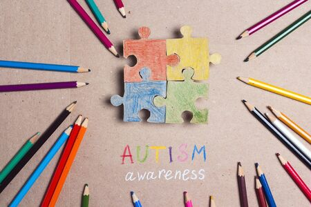 Autism Awareness Day. Colorful puzzle and  and color pencils in autism awareness day. Archivio Fotografico