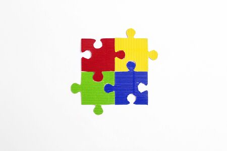 Four colored puzzle pieces on a white background. Autism Awareness Day. Autism Spectrum Disorder (ASD) concept.