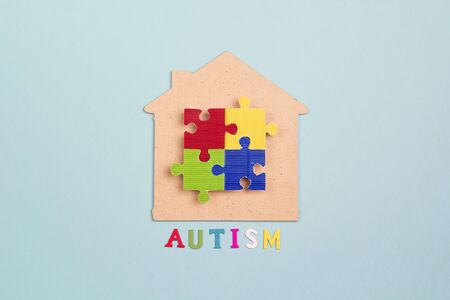 House symbol with colorful puzzle on a blue background. Autism Awareness Day. Autism Spectrum Disorder (ASD) concept.