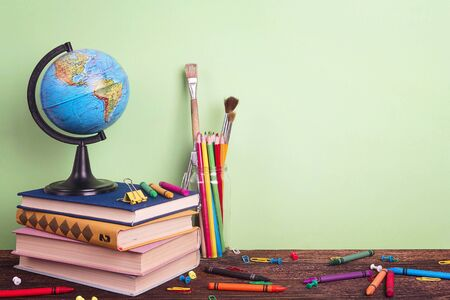 Education composition with a globe, a stack of books and school supplies on a green background. Copy space for text. The concept of the teachers day.