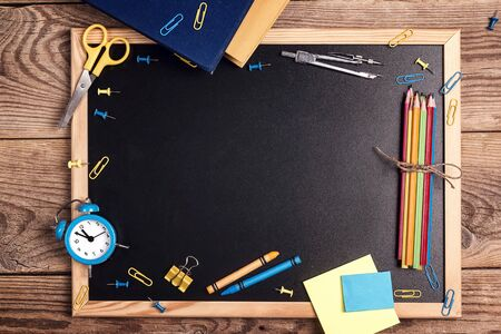 A chalkboard with school supplies and alarm clock on a rustic wooden table. Copy space for text. The concept of the teachers day. Card, invitation or greeting template.