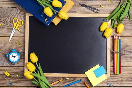 A chalkboard with school supplies and tulip flowers  on a rustic wooden table. Copy space for text. The concept of the teachers day.  写真素材