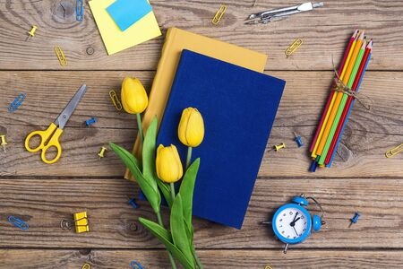 Festive educational background with books, school supplies and tulip flowers on rustic wooden table. The concept of the teachers day. Card, invitation or greeting template.   写真素材