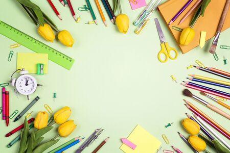 Composition de cadre plat à partir de fournitures scolaires et de tulipes jaunes sur fond vert. Le concept de la journée de l'enseignant. Modèle de carte, d'invitation ou de voeux.