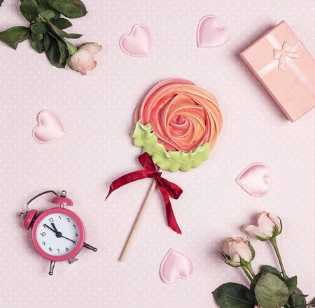 Meringue lollipop flower surrounded by roses, hearts, gift and alarm clock. Festive sweet pink background.