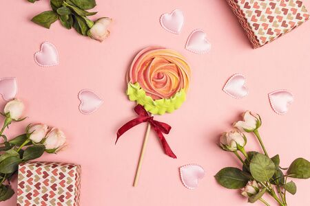 Meringue lollipop flower surrounded by roses, hearts and gifts. Festive sweet pink background.