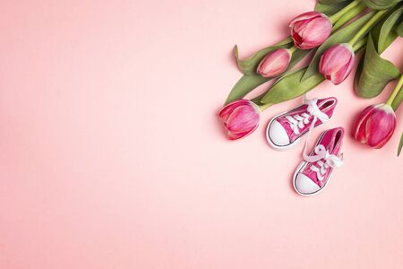 Cute pink baby girl sneakers with tulup flowers on a pink background. Copy space, flat lay, top view. 写真素材