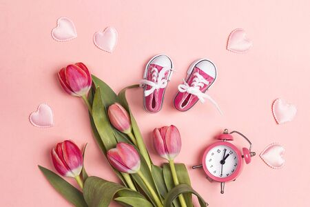 Cute pink baby girl sneakers with tulup flowers and alarm clock on a pink background. Flat lay, top view.