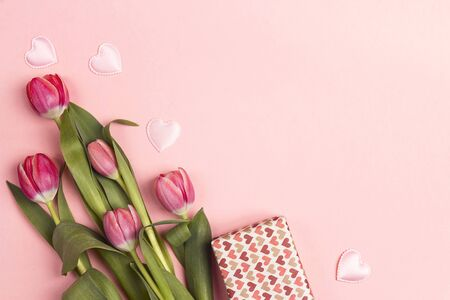 Festive pink background with tulip flowers and a gift. Place for text. Flat lay, top view. 写真素材