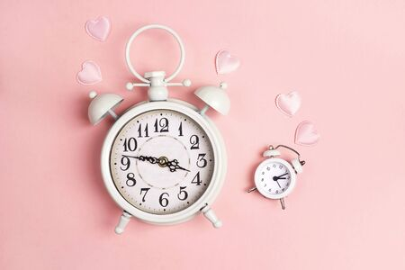 Big and small white alarm clocks like mom and daughter on pink. Mothers Day concept.
