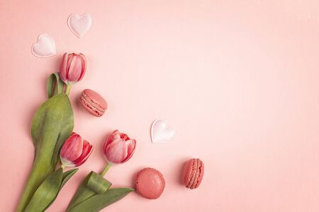 Tulip flowers with macarons on pink background. Place for text. Flat lay, top view.